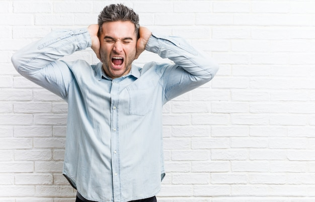 Young handsome man against a bricks wall covering ears with hands trying not to hear too loud sound.