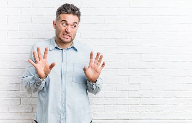 Young handsome man against a bricks wall rejecting someone showing a gesture of disgust.