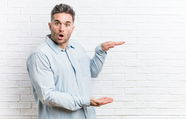Young handsome man against a bricks wall shocked and amazed holding a copyspace between hands.