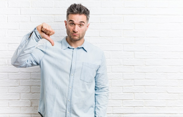 Young handsome man against a bricks wall showing a dislike gesture, thumbs down.