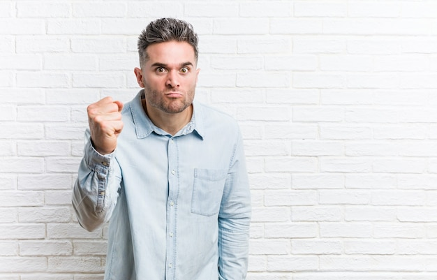 Young handsome man against a bricks wall showing fist to camera, aggressive facial expression.