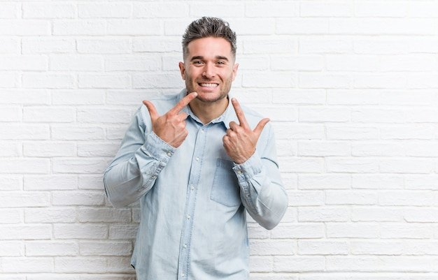 Young handsome man against a bricks wall smiles, pointing fingers at mouth.
