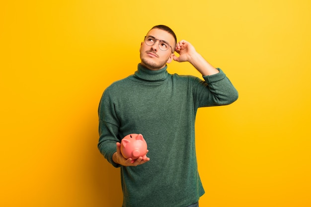 Young handsome man  against flat wall with a piggy bank