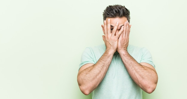 Young handsome man against a green background blink through fingers frightened and nervous.