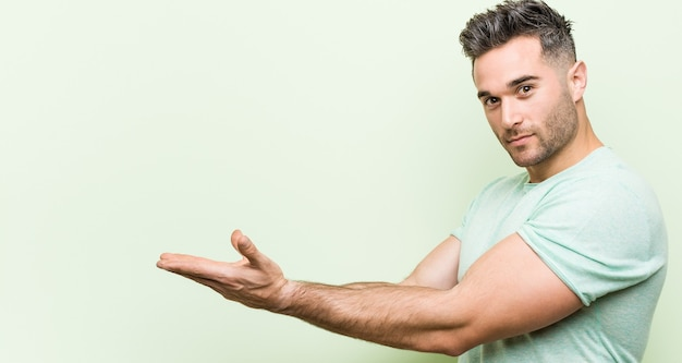 Young handsome man against a green background holding a copy space on a palm.