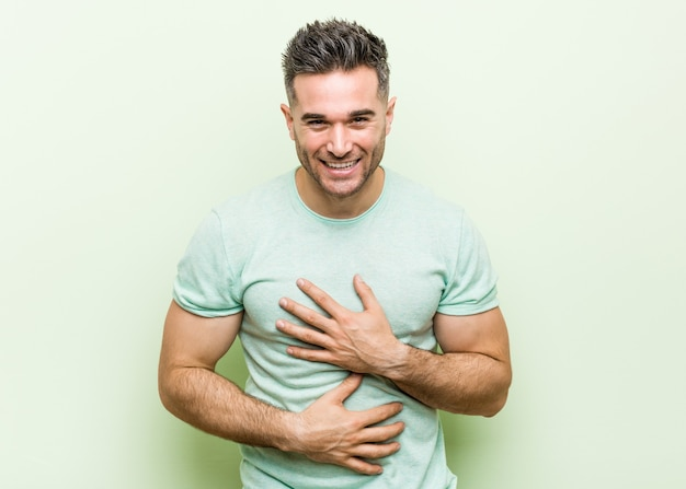 Young handsome man against a green background laughs happily and has fun keeping hands on stomach.