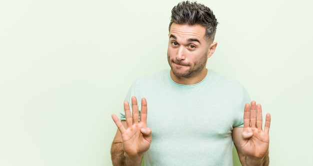 Young handsome man against a green background rejecting someone showing a gesture of disgust.