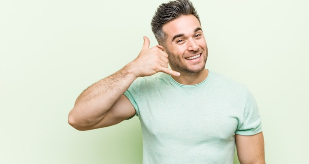 Young handsome man against a green background showing a mobile phone call gesture with fingers.