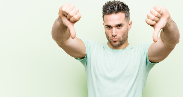 Young handsome man against a green background showing thumb down and expressing dislike.