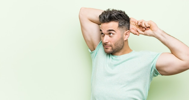Young handsome man against a green background stretching arms, relaxed position.