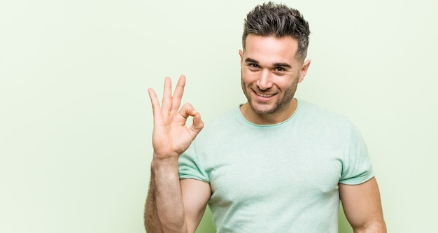 Young handsome man against a green cheerful and confident showing ok gesture.