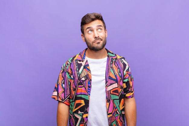 紫色の壁に対して若いハンサムな男
