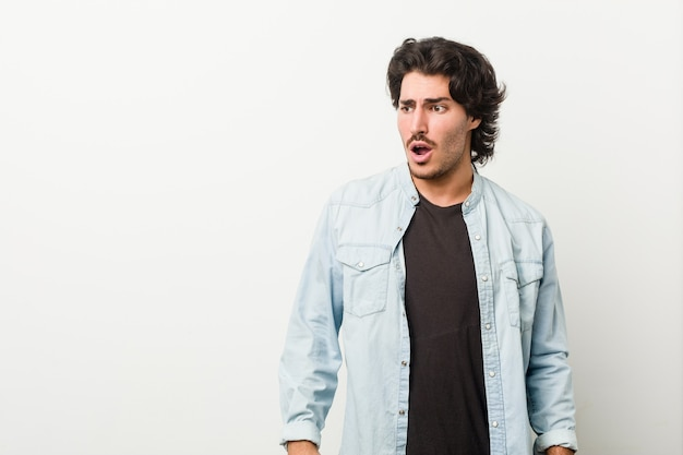 Young handsome man against a white wall being shocked because of something she has seen.