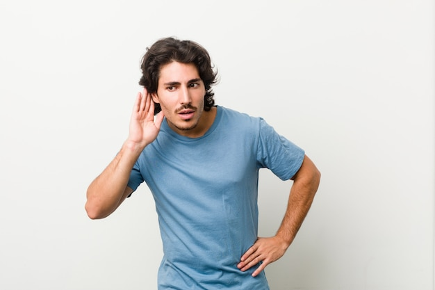Young handsome man against a white wall trying to listening a gossip.