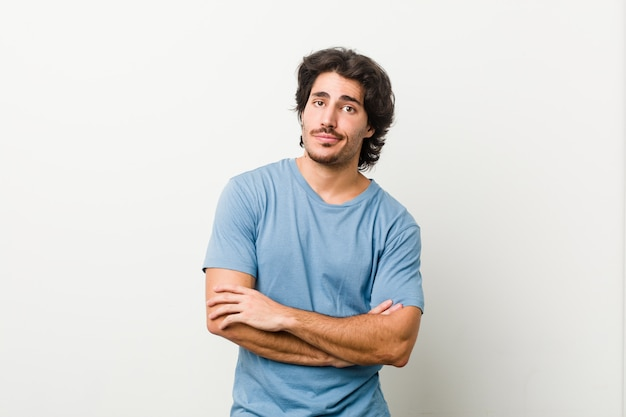 Young handsome man against a white wall unhappy looking in camera with sarcastic expression.