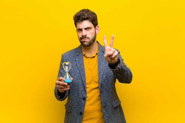 Young handsome man against yellow wall