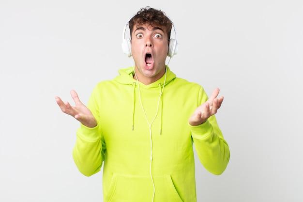 若いハンサムな男は信じられないほどの驚きとヘッドフォンで驚いて、ショックを受けて驚いた