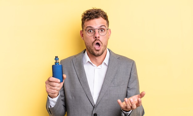 Young handsome man amazed, shocked and astonished with an unbelievable surprise. vaporizer concept