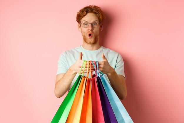 若いハンサムな男は、特別割引、ギフトの購入、買い物袋の持ち方、ピンクの背景の上に立っていることに驚いていました。