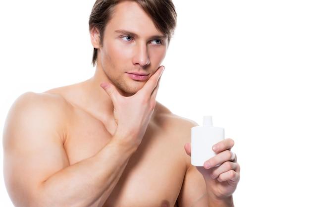 얼굴-화이트 절연 로션을 적용하는 젊은 잘 생긴 남자.