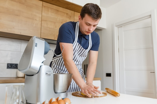 Young handsome man in apron kneading dough in kitchen chef making pastry using utensils at home