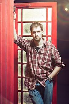 赤い電話ブースで若いハンサムな男