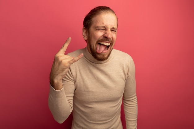 Young handsome man in beige turtleneck crazy happy sticking out tongue making rock symbol standing over pink wall