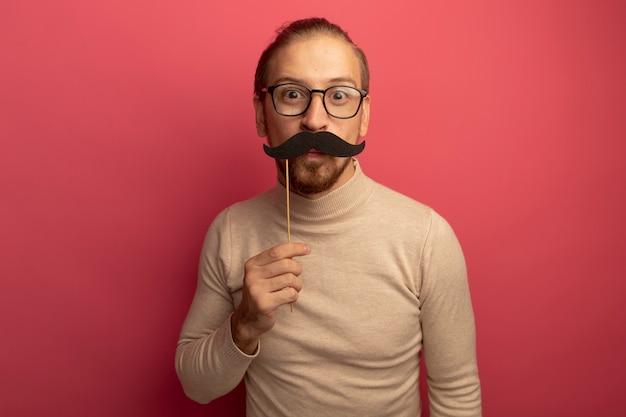 Giovane uomo bello in dolcevita beige e occhiali che tengono i baffi divertenti sul bastone che sta sopra la parete rosa