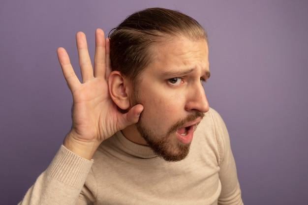 Giovane uomo bello in dolcevita beige che tiene la mano vicino al suo orecchio cercando di ascoltare pettegolezzi in piedi sopra il muro lilla