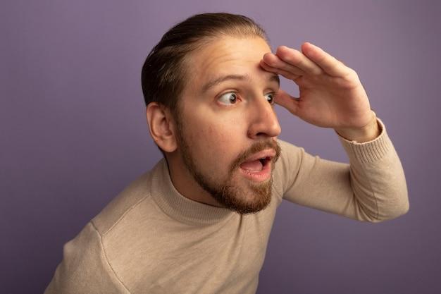 Giovane uomo bello in dolcevita beige che osserva da parte lontano con la mano sopra la testa in piedi sopra il muro lilla
