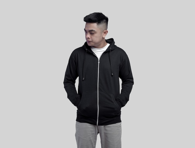 Young handsome man in black hoodie zipper posing in plain wall