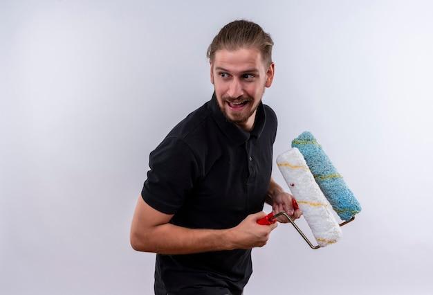 Giovane uomo bello in maglietta polo nera che tiene i rulli di vernice che osserva da parte furbescamente in piedi su sfondo bianco