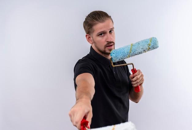 Giovane uomo bello in maglietta polo nera che tiene i rulli di vernice che punta alla telecamera con esso in piedi su sfondo bianco