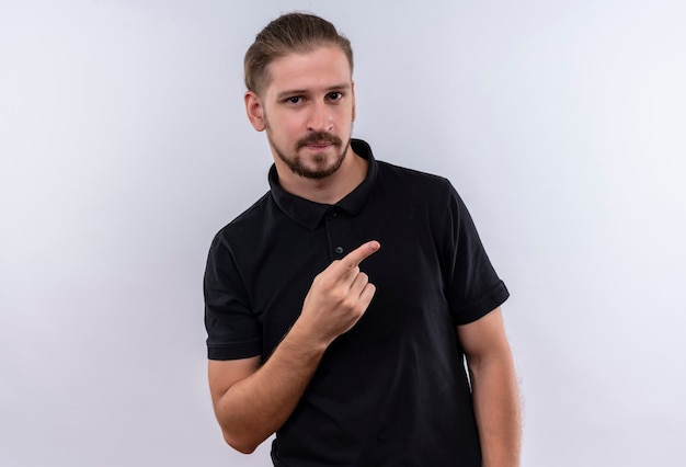 Young handsome man in black polo shirt smiling confident pointing to the side with finger standing over white background