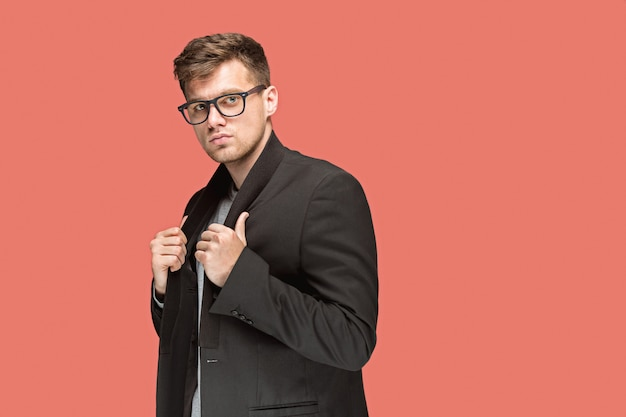 Young handsome man in black suit and glasses isolated on red
