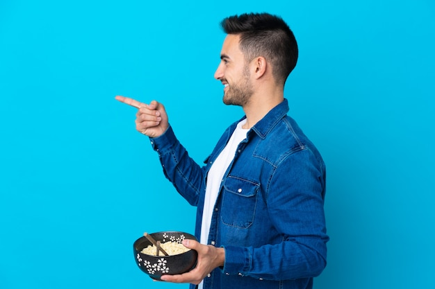 Young handsome man over blue pointing to the side to present a product