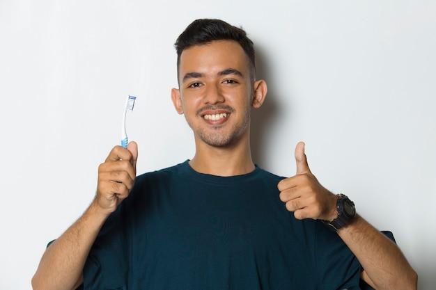 白い背景で隔離の彼の歯を磨く若いハンサムな男