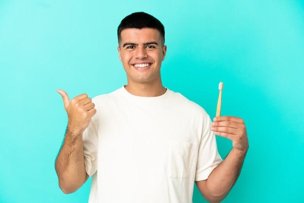 製品を提示する側を指している孤立した青い背景の上に歯を磨く若いハンサムな男 Premium写真
