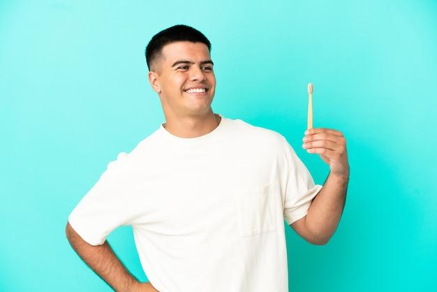 腰に腕と笑顔でポーズをとって孤立した青い背景の上に歯を磨く若いハンサムな男