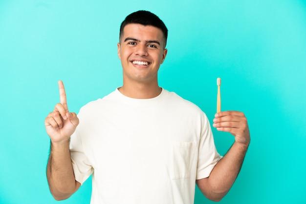 最高の兆候を示して指を持ち上げて孤立した青い背景の上に歯を磨く若いハンサムな男