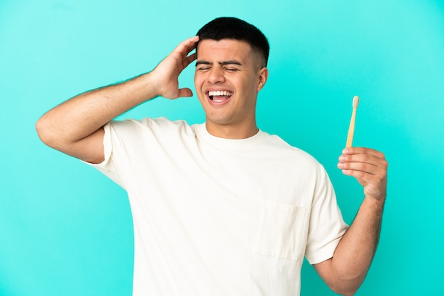 たくさん笑って孤立した青い背景の上に歯を磨く若いハンサムな男