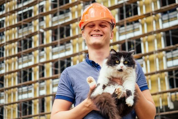 Молодой красавец-строитель в оранжевом шлеме держит кошку