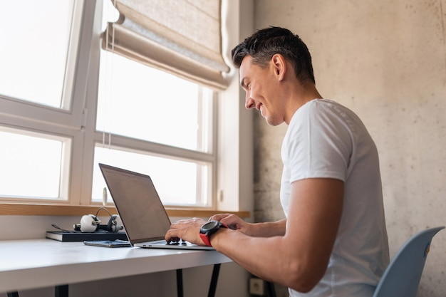 Young handsome man in casual outfit sitting at table working on laptop, freelancer at home