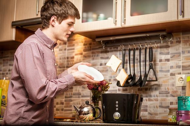 白い皿に新鮮な飛び出たトーストをキャッチする若いハンサムな男