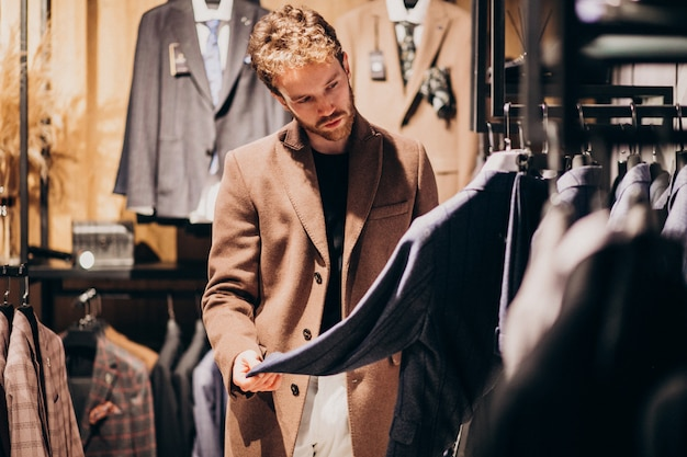 Young handsome man choosing clothes at shop