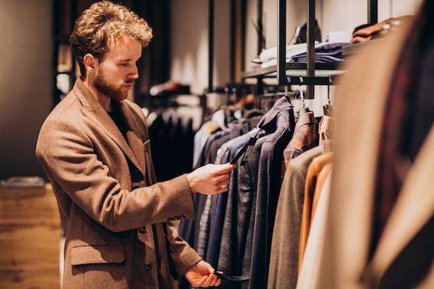 选择衣裳的年轻英俊的人在商店