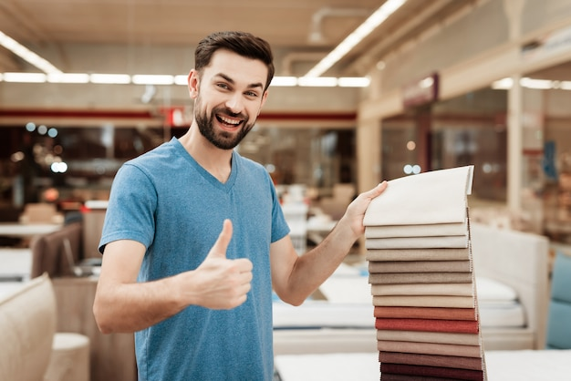 Young handsome man choosing color of mattress