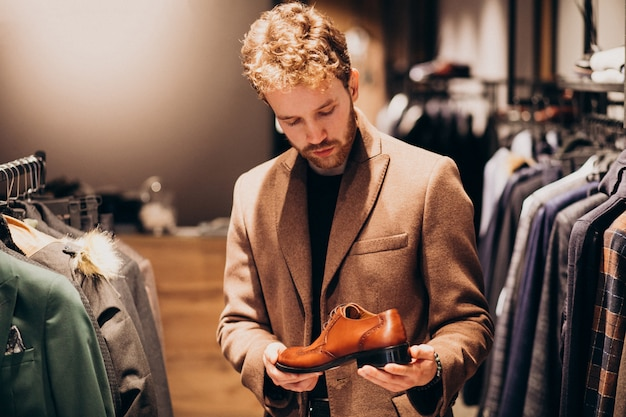 Young handsome man choosing shoes at a shop