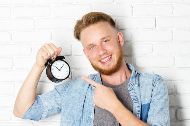 Young handsome man and clock on brick wall