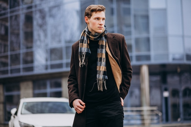 Young handsome man in a coat outside the street